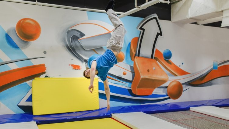 A young man doing fly stunts in trampoline park; Shutterstock ID 558997459